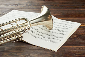 Trumpet and musical notes on wooden background. Classical music objects on brown wooden table. Classical music for studying.