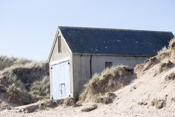 Boat House on Beach in front of Blue Sky