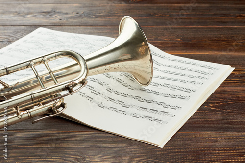 Trumpet and musical notes on wooden background  Classical