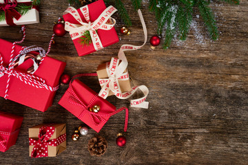 Christmas gift giving concept - christmas presents in red and white boxes on wooden table, flat lay scene