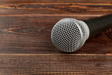 Dynamic microphone on wooden background. Gray microphone on textured wooden table with copy space.