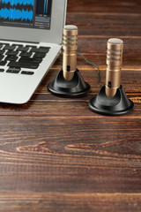 Mini stereo microphones, laptop and copy space. Silver laptop and professional stereo microphones on wooden backgrond, vertical image.