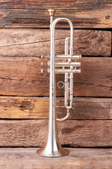 Vintage trumpet on old wooden background. Aged trumpet on rustic wooden boards, vertical image. Classical wind instrument.