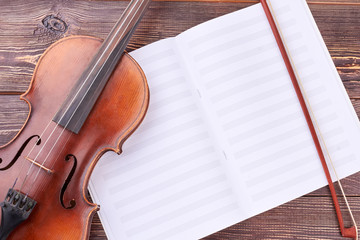 Violin, bow and musical notes. Brown violin and bow on musical sheets. Classical equipment of orchestra.