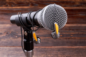 Close up microphone with earphones. Gray microphone and earphones on wooden background. Modern musical technologies.