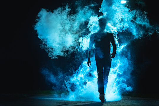 The man walking in the blue smoke on the dark background