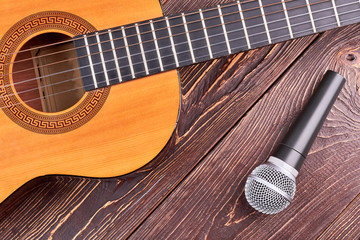 Acoustic guitar and microphone on wooden background. Ukulele guitar and microphone, cropped image. Professional musical equipment.