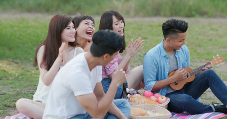 Youngster friends having fun in the picnic time at the park