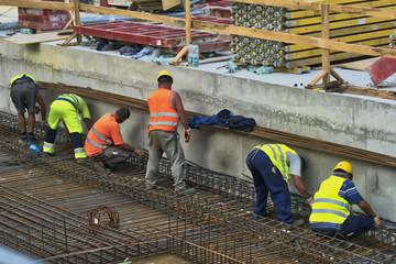 Fototapeta prace budowlane, robotnicy na budowie przy montażu konstrukcji żelbetowej obraz