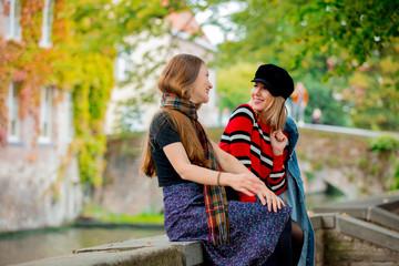 Young girlfriends talking on bridge in Bruges, Belgium. Autumn season