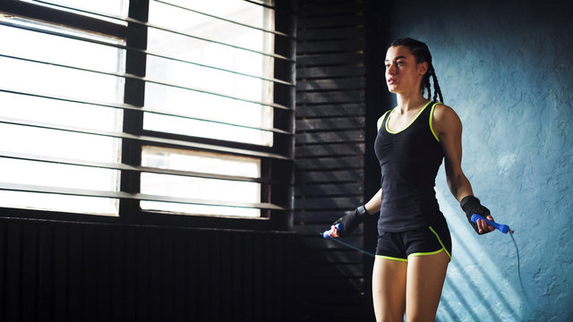 young serious female boxer in wrapped hands warming up, jumping on skipping rope free space, copyspace. Fit woman preparing to boxing competition. Wellness, fighting, motivation, self defense concept