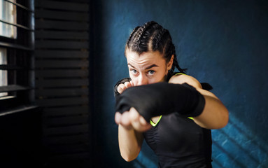 portrait beautiful young boxing woman training punching in gym. Fit female preparing to boxing competition. Wellness, fighting, motivation, martial arts, self defense concept