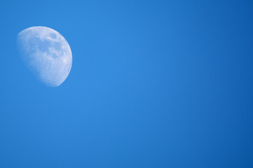 Moon in blue sky with space for text