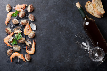 Fresh seafood and white wine on stone table