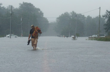 Luis Durban walks with supplies through floodwater caused by Hurricane Florence in Lumberton