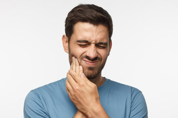 Portrait of young handsome guy solated on gray background, his face distorted and hands pressed to cheek as he is experiencing severe tooth ache and worries about it