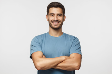 Smiling handsome man in blue t-shirt standing with crossed arms isolated on gray background Wall mural