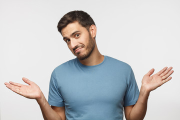 I don't know. Portrait of young confused man in blue t-shirt standing and shrugging shoulders, spreading hands isolated on gray background. I dunno