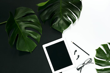 Office workspace layout with tablet accessories on white background, tropical monstera leaves