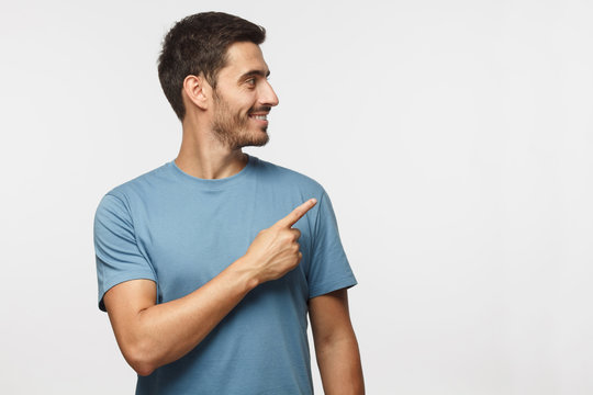 Casual dressed young man in blue t-shirt looking right, pointing with his finger, isolated on gray background with copy space for your text
