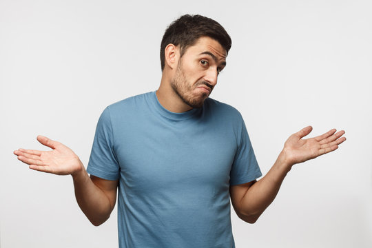 I don't know. Young man isolated on gray background, showing helpless gesture with arm and hands, mouth curved as if he does not know what to do
