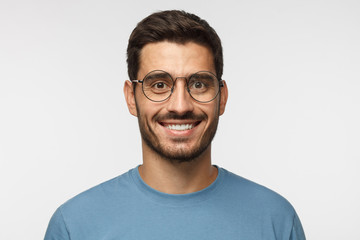 Close up shot of smiling attractive man in blue t-shirt and trendy round eyeglasses isolated on gray background