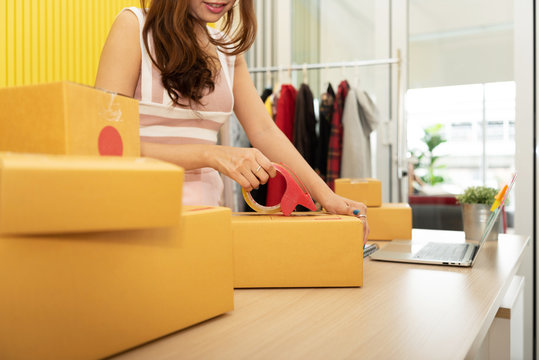 Young Asian woman is packing products in cardboard boxes.