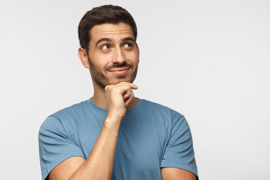 Portrait of young man in blue t-shirt with dreamy cheerful expression, thinking, isolated on gray background with copy space for your ads