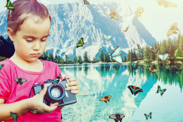 Little girl photographing butterfly with retro photo camera in fairytale forest.