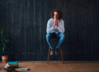 Handsome curly student holds hands on chin while sitting on a chair in a room with the minimalist interior.