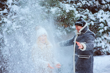 winter portrait of happy couple having lot of fun and throwing snow outdoor in the forest. Winter activities on holidays.