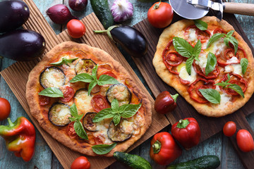 Healthy vegetarian meal. Homemade pizzas with aubergines, bell peppers, mozarella, basil and tomatoes on oak boards with raw ingredients