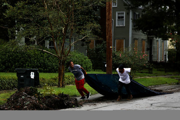 People pull a sheet with debris along the street as they clean their house after the passing of Hurricane Florence in New Bern, North Carolina
