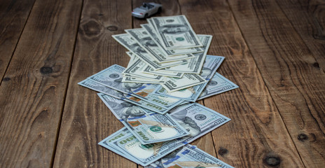 a stack of one hundred dollar bils on wooden background