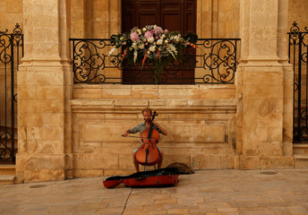 A street musician plays the cello in front of Saint Catherine's Church in Valletta