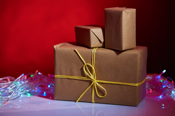 few simple craft Christmas boxes with lights on red background