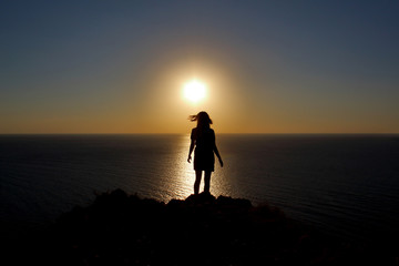young girl is facing the sun on the mountain and looking at the sea, hands raised up and to the side