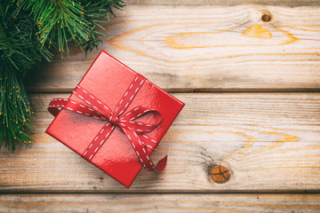 Gift box with red ribbon on wooden background, copy space, top view