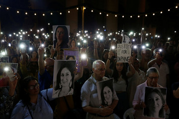 Michael and Rose Vella, parents of assassinated anti-corruption journalist Caruana Galizia, hold photos of their daughter during a vigil to mark eleven months since her murder, in Valletta