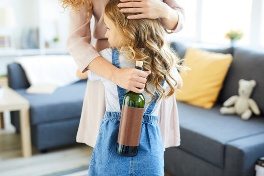 Unsafe little girl embracing her drunk mother holding bottle of wine