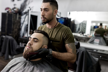 Handsome barber holds his hands on the beard of young brutal man and looks at the mirror at a barbershop