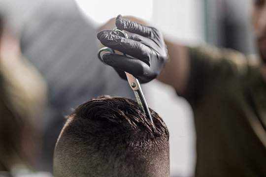 Barber in black gloves cuts with scissors hair on top of head of dark-haired man at a barbershop