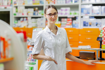 A good-looking slim girl with dark hair and glasses,dressed in a medical overall,stands by the cash desk and looks at hte camera in a up-to-date pharmacy.