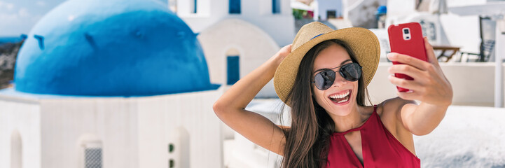 Fototapete - Happy tourist taking selfie having fun on Europe summer vacation in Santorini, cruise destination panoramic banner. Asian woman panoramic banner holding mobile taking picture.