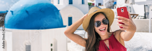 Wall mural Happy tourist taking selfie having fun on Europe summer vacation in Santorini, cruise destination panoramic banner. Asian woman panoramic banner holding mobile taking picture.