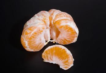 peeled tangerine on black background