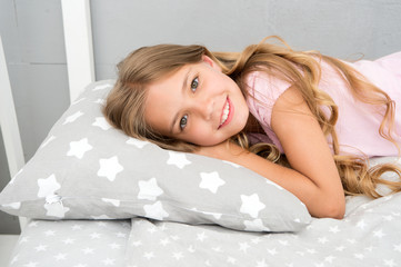 Good morning. Girl child long hair lay awake close up. Quality of sleep depends on many factors. Choose proper pillow to sleep well. Girl on little pillow bedclothes background. Pleasant awakening