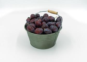 leckere Zwetschgen in einem dekorativen kleinem Eimer.