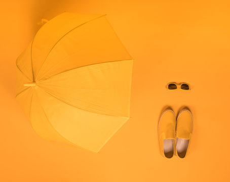 yellow shoes and a yellow umbrella on a yellow background