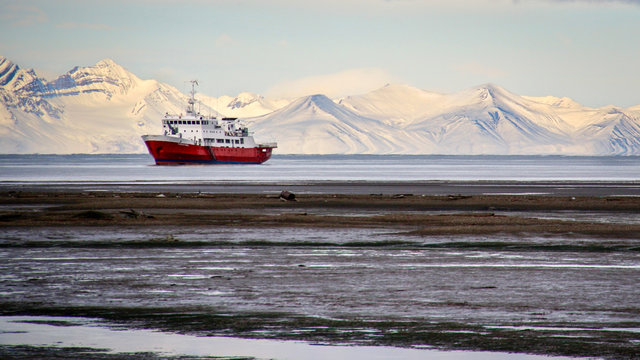 An icebreaker ship sits offshore in front of snow-covered mountains in Longyearbyen, Svalbard, Norwegian Arctic